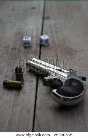 Circa 1889, Model 95, Type II Model 3 Double Derringer, on antique wooden table with shells and dice