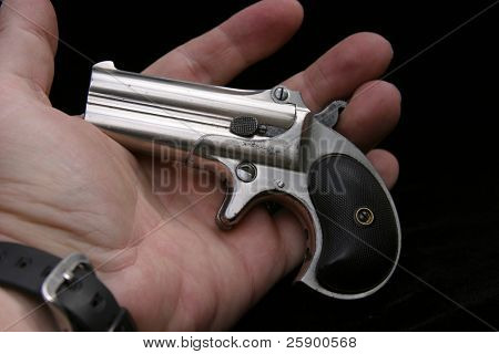 Circa 1889, Model 95, Type II Model 3 Double Derringer, in the palm of a mans hand showing the small size of the gun