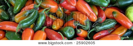 cropped red, orange, and green chillies at a swap meet for sale