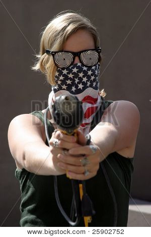 an insane young woman wearing Hypnotic Glasses and an American Flag Bandanna holds an Electric Drill like a Gun at YOU