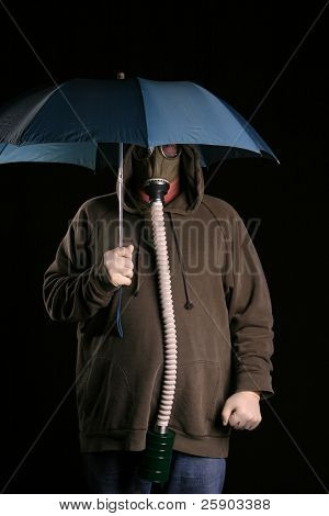 Apocalyptic acid rainy day A man in a gas mask holds a blue umbrella to protect himself from the acid rain in a futuristic nuclear wasteland