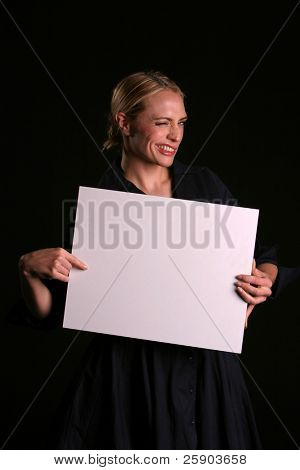 a young blondie woman holds a blank white sign and whinks at you the viewer