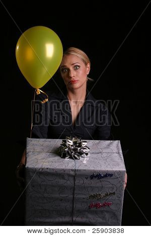 kids birthday concepts boy or girl a young mom gives a large birthday present and a yellow helium balloon