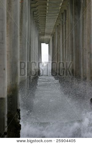 Beneath The world famous Huntington Beach California Pier durring very unusuial high surf and rough weather