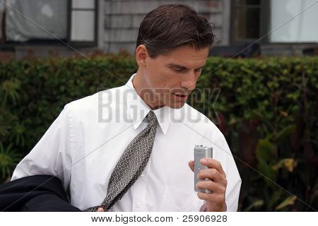 a business man dictates into his miniature tape recorder