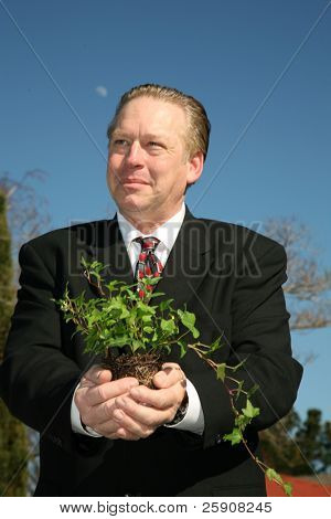 an enviromently friendly business man in a nice suit holds a green plant to save the earth from Global Warming