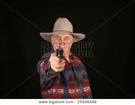 A cowboy points a Colt Navy 44 caliber black powder revolver at YOU THE VIEWER