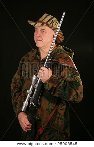 a hunter poses with his trusty rifle against a black background