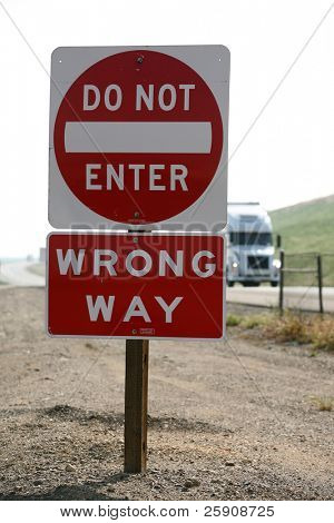 "a ""do not enter"" ""wrong way"" sign on a freeway with a ""semi truck"" behind it"