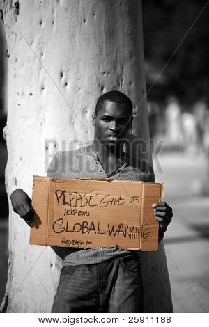 a man asks for donations to help stop Global Warming with his cardboard sign in black and white and colorized