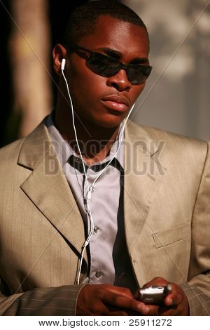a well dressed african american man text messages on his cell phone outside while listening on his personal digital music player