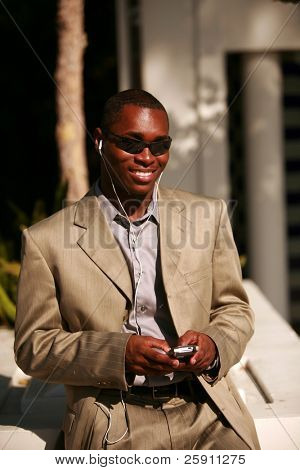 a well dressed african american business man text messages on his cell phone outside while listening on his personal digital music player