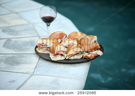 a plate of fresh Submarine Sandwiches with a glass of wine by a nice swimming pool