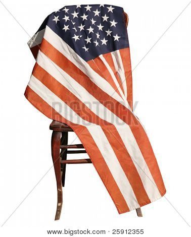 isolated on white, an american flag is draped over a wooden chair
