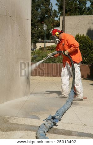 a city worker sand blast away graffiti on a wall