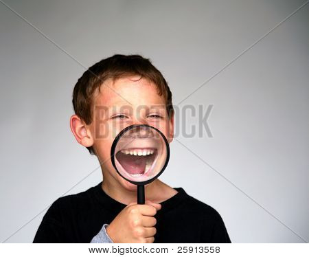 a young boy holds a magnifying glass up to his mouth for a fun and funny photo