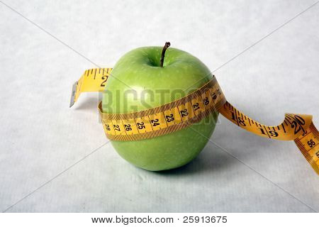 green apple with paper tape measure represents healthy eating and diet
