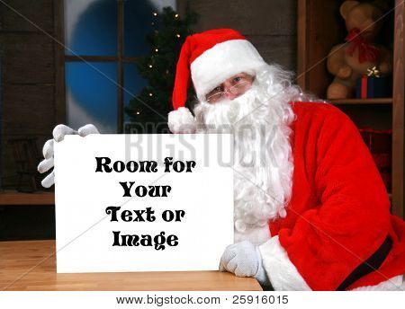 """santa claus"" holds a blank white sign with ""room for your text or image""  while in his workshop in the ""north pole"""