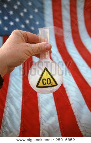 a hand holds a 500ml flask filled with Carbon Dioxide aka CO2 releasing it into the autmosphere over an american flag