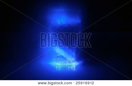 time laps exposure of a neon blue glowing drink cup bubbling with dry ice and fog in a pitch black room