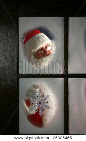 Santa Claus looks out through the snow and fog on his workshop window in the north pole to see outside check the weather while he holds up a large snow flake  on December 24th, Christmas Eve