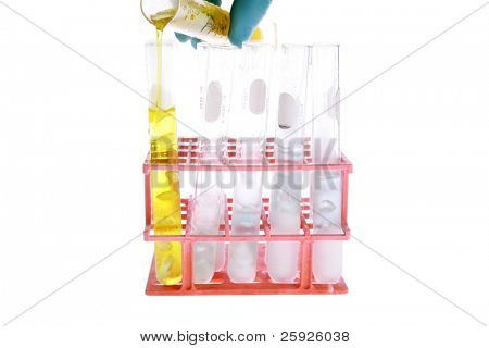 a chemist or medical research scientist adds chemicals to a
