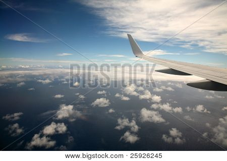 the view out the window of an airplane on the way to Maui Hawaii at 30,000 feet in the air over the pacific ocean