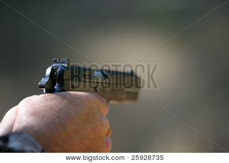 an unidentifiable person shoots a high power pistol. low depth of field photo so the background in out of focus and focus is on the gun