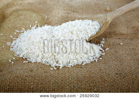 uncooked white rice on a wooden spoon on a burlap bag.