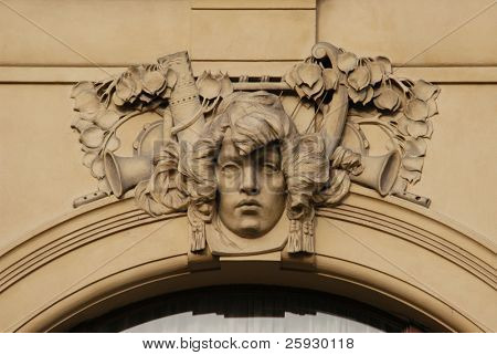 Allegory of music, a stucco mask on the facade of the Municipal House in Prague, Czech Republic