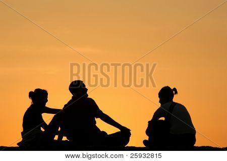Silhouetted company talking at sunset