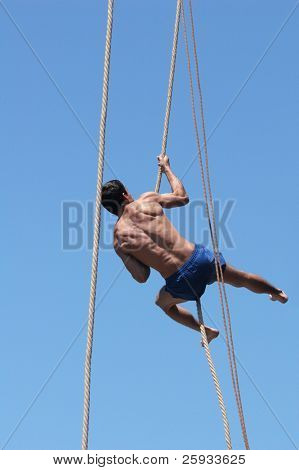Shirtless athlete climbing up the rope