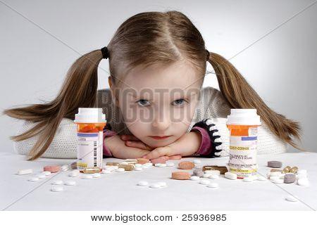 Sad little girl behind pile of medicine