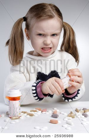 Angry little girl trying to medicine bottle.
