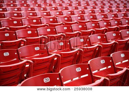Empty rows of vivid red chairs with numbers.