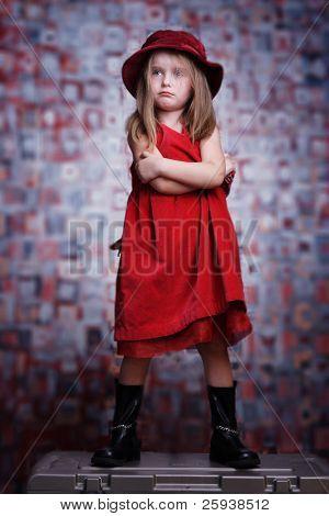 Upset cute little girl in red dress.