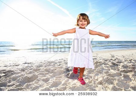 Small happy girl in white dress enjoying sunny day at the beach. Shoot against the sun.
