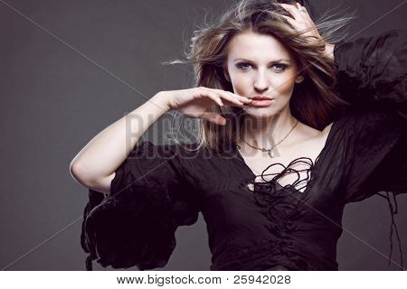 Young attractive fashion model posing on dark background.