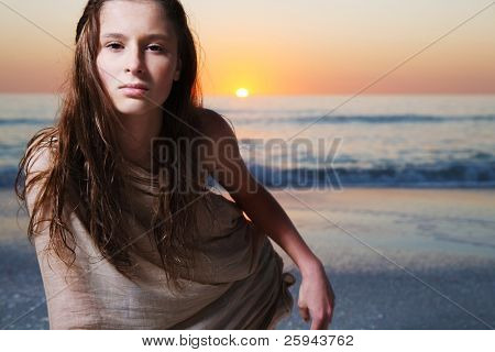 Young happy girl with long hair enjoys summer day at the beach.