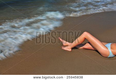 Beautiful legs of a girl and surf with longer exposure