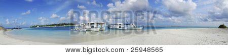 Beautiful white Maldivian beach and five dhoni ships docked nearby