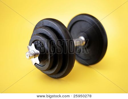 Metallic dumbell on yellow surface. Very short depth-of-field.