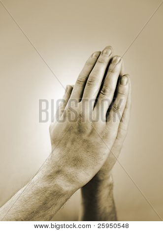 Sepia toned photograph of hand clasped in prayer