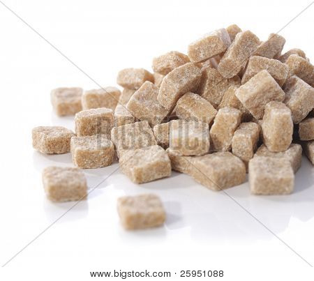 Natural brown sugar cubes on white reflecting background.