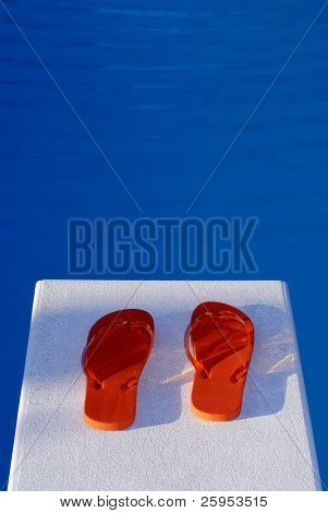 Pair Of Flip Flop Thongs On A Diving Board At A Swimming Pool