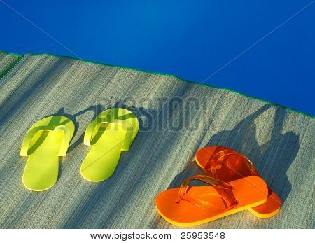 Yellow And Orange Pair Of Flip Flop Thongs By The Side Of A Swimming Pool