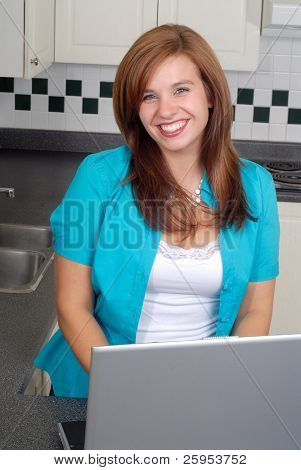Attractive Young Woman Working On Her laptop Computer At Home In The Kitchen