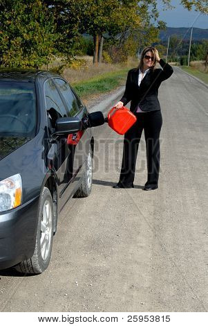 Businesswoman At The Side Of The Road Filling Her Car With Gas From A Gas Can