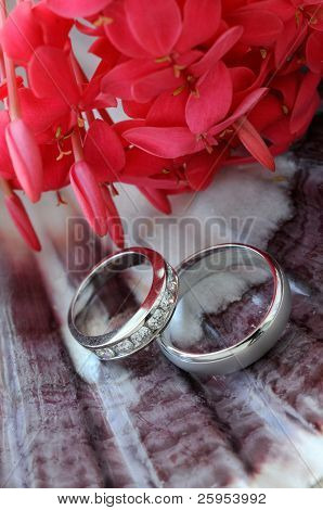 Man And Womans Wedding Rings On A Sea Shell With Flowers