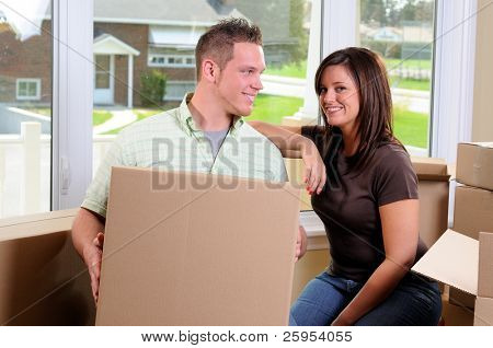 Young Couple Moving Into Their New Home Surrounded By Cardboard Boxes